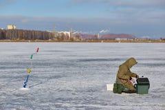 Pêche de glace d'homme sur un lac congelé images libres de droits