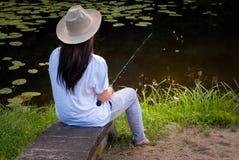 Pêche de jeune femme dans l'étang en été Photographie stock