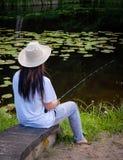 Pêche de jeune femme dans l'étang en été Photo stock