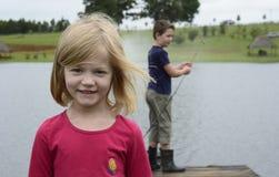 Pêche de jeune fille et de garçon sur le pilier en bois photographie stock