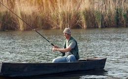Pêche de jeune homme de pêcheur sur la rivière Image stock