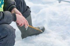 Pêche de l'hiver Un outil pour la pêche d'hiver dans des mains Une canne à pêche dans les mains pour la congélation Photos stock