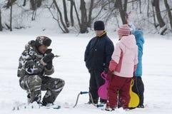 Pêche de l'hiver. Vieux pêcheur et jeunes spectateurs Image libre de droits