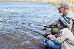 Pêche de père et de fils à un lac Photographie stock