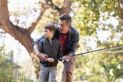 Pêche de père et de fils dans la forêt Photographie stock