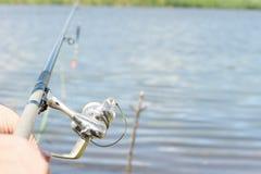 Pêche de pêcheur à la ligne avec une tige et une bobine de rotation Photo stock