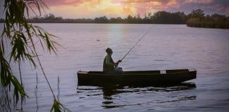 Pêche de pêcheur sur la banque de la rivière au coucher du soleil Photographie stock libre de droits