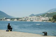 Pêche de pêcheur sur un quai dans Herceg Novi, faisant face à la station de vacances d'Igalo, sur la Mer Adriatique Herceg Novi e photo libre de droits