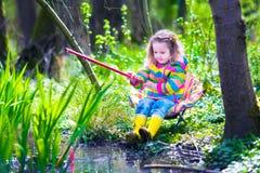 Pêche de petite fille dans une forêt Photographie stock libre de droits