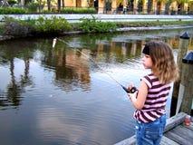 Pêche de petite fille outre de dock Image stock