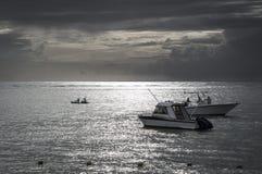 Pêche des bateaux blancs en mer au coucher du soleil Photos libres de droits