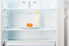Pêche du plat blanc avec la bouteille de yaourt dans le réfrigérateur Photographie stock libre de droits