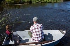 Pêche heureuse d'homme avec son fils Image stock