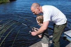 Pêche heureuse d'homme avec son fils Photos stock