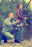 Pêche heureuse d'homme sur la rivière d'eau douce du rivage Image libre de droits