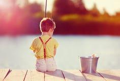 Pêche mignonne de petit garçon sur l'étang au coucher du soleil Photos stock