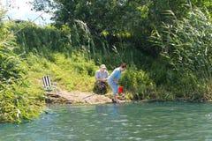 Pêche pluse âgé de couples sur un lac d'eau douce tranquille Images libres de droits