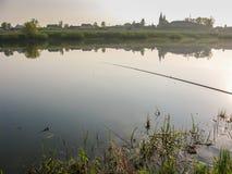Pêche pour l'amorce dans un matin magique tranquille de ressort du rivage du lac Photographie stock