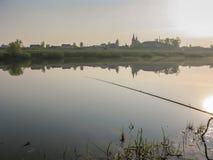Pêche pour l'amorce dans un matin magique tranquille de ressort du rivage du lac Photos stock
