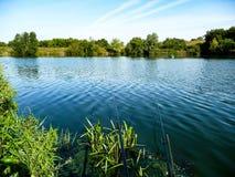 Pêche sur le rivage d'un étang avec les cannes à pêche Photos stock