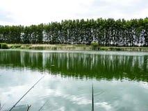 Pêche sur le rivage d'un étang avec les cannes à pêche Images libres de droits