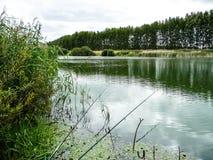 Pêche sur le rivage d'un étang avec les cannes à pêche Images stock