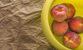 Pêches dans une tasse en plastique jaune sur un papier brun images libres de droits