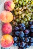 Pêches et raisins dans un plat sur la table Photographie stock
