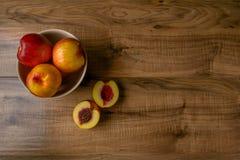 Pêches mûres fraîches d'un plat brun, la table en bois Photo stock