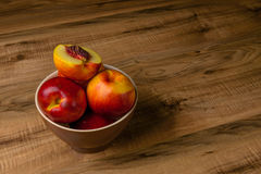 Pêches mûres fraîches d'un plat brun, la table en bois Image libre de droits