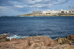 Pêcheur à la ligne avec la canne à pêche blanche dans les roches Mer bleue avec la mousse, village côtier Ciel nuageux, autum La  images libres de droits