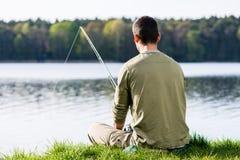Pêcheur à la ligne s'asseyant dans l'herbe à la pêche de lac avec sa tige Images stock