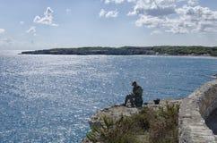 Pêcheur à la ligne solitaire occupé dans la préparation d'amorce Image libre de droits
