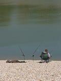 Pêcheur appréciant la paix au rivage de lac images libres de droits