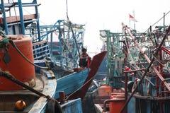 Pêcheur attachant le tissu rouge à la proue du bateau parmi beaucoup de bateaux de pêche amarrés dans le port gauche, Jakarta photographie stock libre de droits