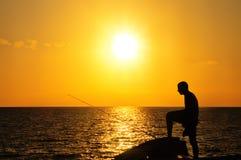 Pêcheur au coucher du soleil Photos stock