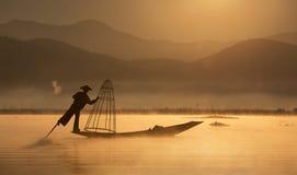 Pêcheur avec le réseau traditionnel sur le vieux bateau à l'aube à image stock
