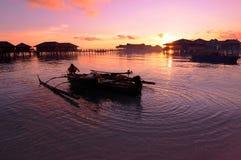 Pêcheur avec son bateau pendant le coucher du soleil Photographie stock