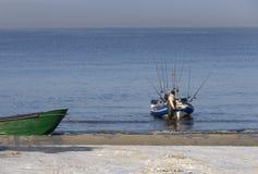 Pêcheur avec un bateau et des cannes à pêche sur le rivage de la mer baltique un jour ensoleillé dans la ville de Klaipeda, Lithu images stock