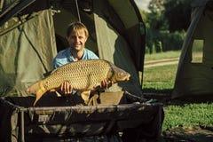 Pêcheur avec un trophée Pêche de carpe, pêchant, capture de poissons Photos stock