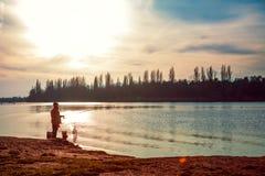 Pêcheur avec une canne à pêche sur la berge Beau ciel images stock