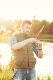 Pêcheur avec une tige et une amorce de rotation Images stock