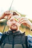 Pêcheur avec une tige et une amorce de rotation Photos stock