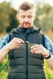 Pêcheur avec une tige et une amorce de rotation Image stock