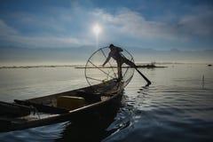 Pêcheur birman sur les poissons contagieux de bateau en bambou de la manière traditionnelle avec le filet fait main Photographie stock libre de droits