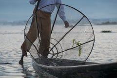 Pêcheur birman sur les poissons contagieux de bateau en bambou de la manière traditionnelle avec le filet fait main Photos stock