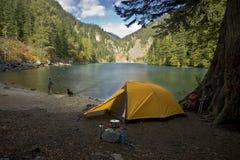 Pêcheur campant à un lac de région sauvage Image stock