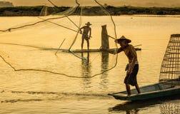Pêcheur dans l'action en pêchant dans le lac Image stock