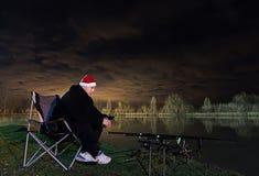 Pêcheur dans la nuit étoilée avec le chapeau de Santa regardant sur des tiges, la patience Photographie stock libre de droits