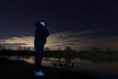 Pêcheur dans la nuit étoilée regardant sur des tiges, la patience Image libre de droits
